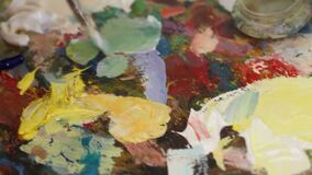 Ο καλλιτέχνης χρωματίζει μια ελαιογραφία σε ένα στούντιο, ζωγράφος στην εργασία, ο δημιουργός κάνει το κομμάτι της τέχνης, των βο φιλμ μικρού μήκους