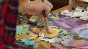 Ο καλλιτέχνης χρωματίζει μια ελαιογραφία σε ένα στούντιο, ζωγράφος στην εργασία, ο δημιουργός κάνει το κομμάτι της τέχνης, των βο απόθεμα βίντεο