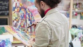 Ο καλλιτέχνης χρωματίζει μια ζωγραφική σε έναν καμβά, που στέκεται πίσω από easel Ακαδημία τέχνης ή σχολείο σχεδίων έμπνευση ταλέ φιλμ μικρού μήκους
