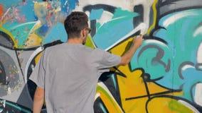 Ο καλλιτέχνης χρωματίζει μια κίτρινη επιστολή στον τοίχο, κλείνει επάνω απόθεμα βίντεο