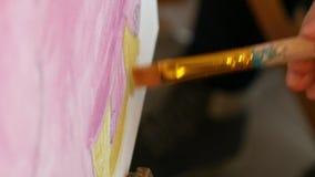 Ο καλλιτέχνης χρωματίζει τον καμβά έργου τέχνης εικόνων στο στούντιο τέχνης απόθεμα βίντεο