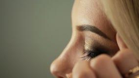 Ο καλλιτέχνης Makeup αιθουσών ομορφιάς κολλά eyelashes στα ξανθά μάτια απόθεμα βίντεο