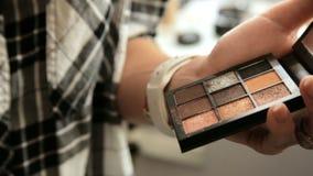 Ο καλλιτέχνης Makeup αιθουσών ομορφιάς χρωματίζει τις σκιές στα μάτια με μια ξανθή γυναίκα βουρτσών απόθεμα βίντεο