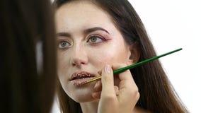 Ο καλλιτέχνης Makeup βάζει το κομφετί στα χείλια Το κομφετί στα χείλια, όμορφα κάνει το επάνω και φωτεινό colorer των χειλιών φιλμ μικρού μήκους