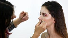 Ο καλλιτέχνης Makeup βάζει το κομφετί στα χείλια Το κομφετί στα χείλια, όμορφα κάνει το επάνω και φωτεινό colorer των χειλιών απόθεμα βίντεο