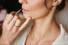 Ο καλλιτέχνης Makeup εφαρμόζει το μοντέρνο γάμο makeup για το όμορφο πρότυπο κορίτσι brunette με το τέλειο δέρμα, γαμήλια προετοι στοκ εικόνες