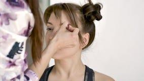 Ο καλλιτέχνης Makeup κάνει makeup ενός όμορφου νέου καυκάσιου brunette απόθεμα βίντεο
