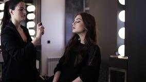 Ο καλλιτέχνης Makeup με τη μαύρη ουρά πόνι χρησιμοποιεί έναν τύπο τελειώνοντας επάνω τον ψεκασμό και τον ψεκάζει ήπια στο πρόσωπο απόθεμα βίντεο