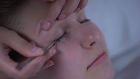 Ο καλλιτέχνης Makeup που κολλά ήπια τα ψεύτικα eyelashes, που συμπληρώνουν την ομορφιά του προτύπου κοιτάζει φιλμ μικρού μήκους