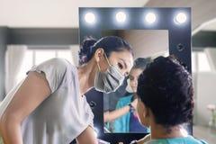 Ο καλλιτέχνης Makeup προετοιμάζει τον πελάτη της πριν από το γάμο στοκ εικόνες με δικαίωμα ελεύθερης χρήσης