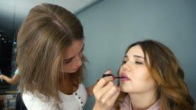 Ο καλλιτέχνης Makeup χρωματίζει τα χείλια για το κορίτσι φιλμ μικρού μήκους