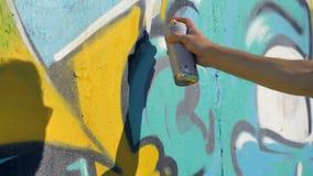 Ο καλλιτέχνης ` s δεξής χρωματίζει μια κίτρινη επιστολή στον τοίχο, άποψη από τον αριστερό, κλείνει επάνω φιλμ μικρού μήκους