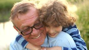 Ο καλός σγουρός εγγονός αγκαλιάζει τον παππού του Ένας συνταξιούχος στα οπτικά γυαλιά με τον εγγονό του ένας μαθητής στον ποταμό απόθεμα βίντεο