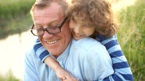 Ο καλός σγουρός εγγονός ψιθυρίζει τα μυστικά του στο αυτί στον παππού του Ο παππούς και ο εγγονός στηρίζονται στη φύση φιλμ μικρού μήκους