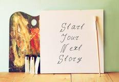 Ο καμβάς με τη φράση αρχίζει την επόμενη ιστορία σας δίπλα στα ελαιοχρώματα και την παλέτα στοκ φωτογραφίες