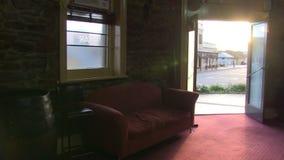 Ο καναπές μέσα σε ένα σπίτι και την πόρτα είναι ανοικτός απόθεμα βίντεο