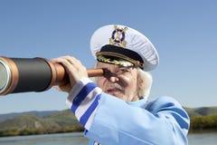 Ο καπετάνιος κοιτάζει μέσω ενός τηλεσκοπίου Στοκ Φωτογραφία
