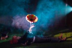 Ο καπελάς βρίσκεται σε ένα μαγικό δάσος με ένα τεράστιο λουλούδι Στοκ φωτογραφία με δικαίωμα ελεύθερης χρήσης