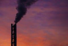 Ο καπνός βγαίνει από το σωλήνα, ενάντια στον ουρανό βραδιού Στοκ Εικόνες