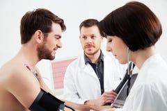 Ο καρδιολόγος και η νοσοκόμα εκτελούν τη δοκιμή πίεσης σε έναν ασθενή στοκ φωτογραφία