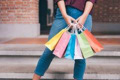 Ο καταναλωτής και η έννοια τρόπου ζωής αγορών, ευτυχής νέα γυναίκα που στέκεται και που κρατά τις ζωηρόχρωμες αγορές τοποθετούν ν στοκ εικόνες με δικαίωμα ελεύθερης χρήσης