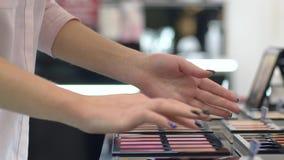 Ο καταναλωτισμός, γυναίκα αγοραστών επιλέγει το blusher για το ίδρυμα makeup και εξεταστικός στο βραχίονα στο κατάστημα καλλυντικ φιλμ μικρού μήκους