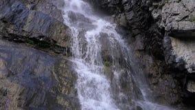 Ο καταρράκτης είναι στενός επάνω, οι πτώσεις νερού και οι ροές κάτω από τους βράχους απόθεμα βίντεο
