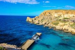 Ο καταρρεσμένος λιμενοβραχίονας, κύματα, βράχοι στον κόλπο αγκύρων στο μεσογειακό νησί της Μάλτας στοκ εικόνες