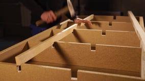 Ο κατασκευαστής επίπλων καθορίζει μια ξύλινη ακτίνα μέσα σε μια κατασκευή του πλαισίου καναπέδων απόθεμα βίντεο