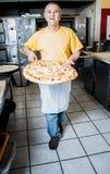 Ο κατασκευαστής πιτσών αφαιρεί μια φρέσκια πίτσα από το φούρνο στοκ φωτογραφίες