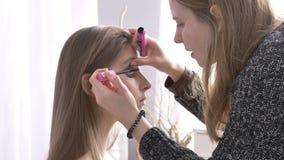 Ο καυκάσιος καλλιτέχνης Makeup χρωματίζει τα μάτια της όμορφης νέας κινηματογράφησης σε πρώτο πλάνο 50 γυναικών brunette fps απόθεμα βίντεο