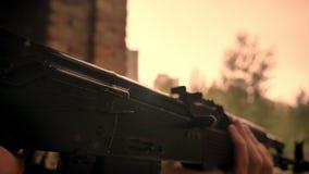 Ο καυκάσιος μαχητής που ντύνεται στην κάλυψη εξετάζει το πυροβόλο όπλο του κρατώντας το και στεμένος μόνους κοντινούς τους τουβλό απόθεμα βίντεο