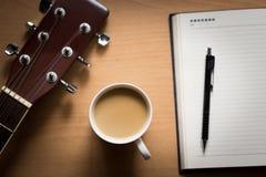 Ο καυτός καφές με την κιθάρα και το σημειωματάριο στο χρόνο επιτραπέζιων σπασιμάτων για σκέφτονται στοκ εικόνες