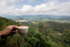 Ο καυτός καφές σε ένα φλυτζάνι κρατούσε από το αριστερό χέρι μπροστά από τη θέα βουνού τοπίων στοκ εικόνα με δικαίωμα ελεύθερης χρήσης