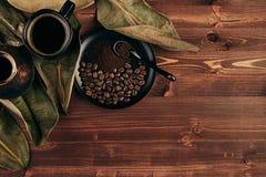 Ο καυτός καφές στο μαύρο φλυτζάνι με τα φασόλια, ξεραίνει τα φύλλα και το τουρκικό δοχείο cezve με το διάστημα αντιγράφων στο καφ Στοκ Φωτογραφία