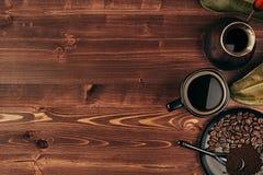 Ο καυτός καφές στο μαύρο φλυτζάνι με τα φασόλια, ξεραίνει τα φύλλα και το τουρκικό δοχείο cezve με το διάστημα αντιγράφων στο καφ Στοκ εικόνα με δικαίωμα ελεύθερης χρήσης