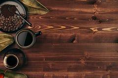 Ο καυτός καφές στο μαύρο φλυτζάνι με τα φασόλια, ξεραίνει τα φύλλα και το τουρκικό δοχείο cezve με το διάστημα αντιγράφων στο καφ Στοκ Εικόνες