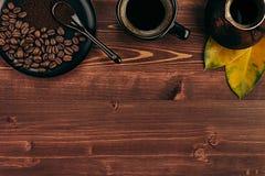 Ο καυτός καφές στο μαύρο φλυτζάνι με τα φασόλια, ξεραίνει τα φύλλα και το τουρκικό δοχείο cezve με το διάστημα αντιγράφων στο καφ Στοκ Φωτογραφίες