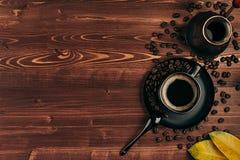 Ο καυτός καφές στο μαύρο φλυτζάνι με τα φασόλια, ξεραίνει τα φύλλα και το τουρκικό δοχείο cezve με το διάστημα αντιγράφων στο καφ Στοκ φωτογραφία με δικαίωμα ελεύθερης χρήσης
