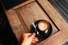 Ο καυτός καφές latte στον ξύλινο πίνακα με δεξή εξυπηρετεί Στοκ Φωτογραφίες