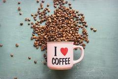 """Ο καφές αγάπης επιγραφής """"Ι """"σε ένα ρόδινο φλυτζάνι που περιβάλλεται από τα φασόλια καφέ o στοκ φωτογραφία με δικαίωμα ελεύθερης χρήσης"""