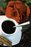 Ο καφές, κανέλα, κέικ φασολιών και αυξήθηκε στο ξύλινο γραφείο Στοκ φωτογραφία με δικαίωμα ελεύθερης χρήσης