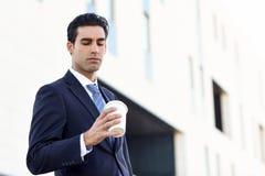 Ο καφές κατανάλωσης επιχειρηματιών για να πάει με παίρνει μαζί το φλυτζάνι Στοκ Φωτογραφία
