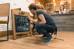 Ο καφές με σας, γράφει στην κιμωλία στο νέο άνδρα εργαζόμενος πινάκων του σπιτιού καφέ στοκ εικόνα με δικαίωμα ελεύθερης χρήσης