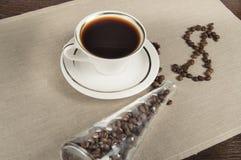 Ο καφές δολαρίων δημιουργείται από τα φασόλια καφέ Φλιτζάνι του καφέ και ένα βάζο γυαλιού με τα φασόλια καφέ Στοκ Φωτογραφία