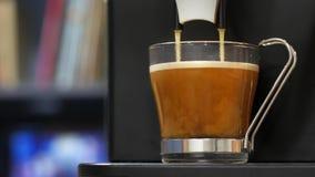 Ο καφές που γίνεται με μια επαγγελματική μηχανή καφέ περιέρχεται σε ένα φλυτζάνι καφέ γυαλιού Κινηματογράφηση σε πρώτο πλάνο απόθεμα βίντεο