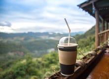 Ο καφές στον πίνακα στο πεζούλι πέρα από το τοπίο βουνών Στοκ εικόνες με δικαίωμα ελεύθερης χρήσης