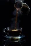 Ο καφές χύνεται σε ένα φλυτζάνι γυαλιού από τους Τούρκους, ένα μαύρο υπόβαθρο στοκ φωτογραφίες με δικαίωμα ελεύθερης χρήσης