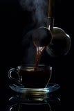 Ο καφές χύνεται σε ένα φλυτζάνι γυαλιού από τους Τούρκους, ένα μαύρο υπόβαθρο στοκ εικόνα