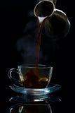 Ο καφές χύνεται σε ένα φλυτζάνι γυαλιού από τους Τούρκους, ένα μαύρο backgr στοκ φωτογραφία με δικαίωμα ελεύθερης χρήσης